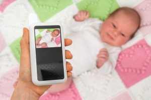 mother holding baby monitor for two rooms for safety of her baby